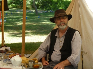 A good photo of a gentleman wearing Civil War era reproduction clothing: shirt, vest, hat, dark trousers, and boots.